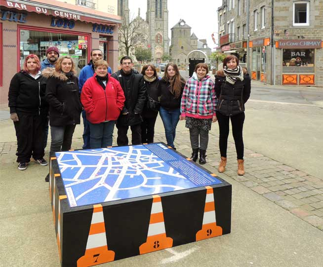 Photographie du groupe Elan's devant la carte de positionnement des œuvres artistiques